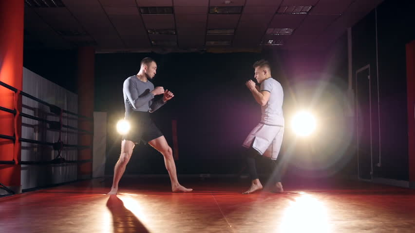 Slow motion. MMA fighters sparring in the ring in darkness.