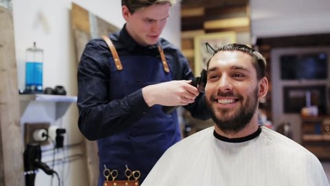 beauty, hairstyle and people concept - happy smiling man and stylist or hairdresser with trimmer doing haircut at hair salon or barber shop