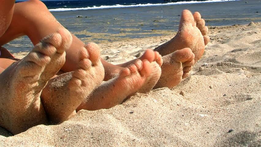 Group of dancing feet on beach.