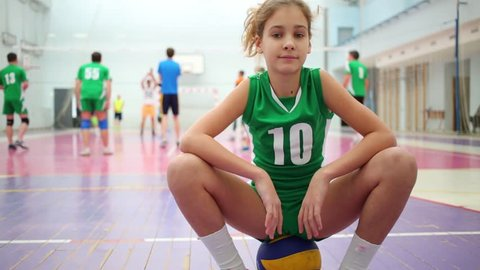Beautiful little girl in uniform is sitting on the ball behind volleyball players.