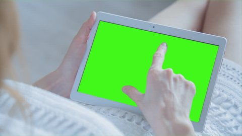 Young Woman laying on a couch uses tablet PC with pre-keyed green screen. Few types of motion - scrolling up and down, tapping, zoom in and out. Perfect for screen compositing. 10bit ProRes 444.