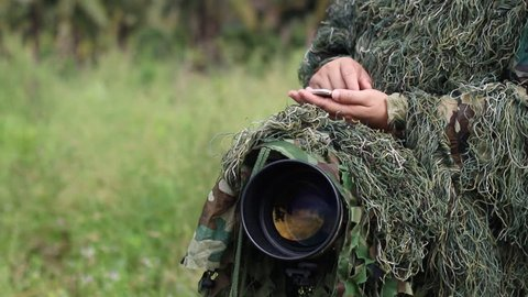 ornithologist in the ghillie suit using smartphone