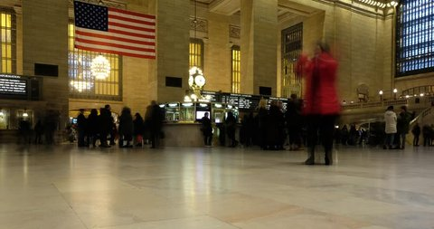 New York City - 12 January 2017: Time lapse of interior of Grand Central Station on 42nd Street, New York. Iconic clock and American flag inside Grand Central Terminal.