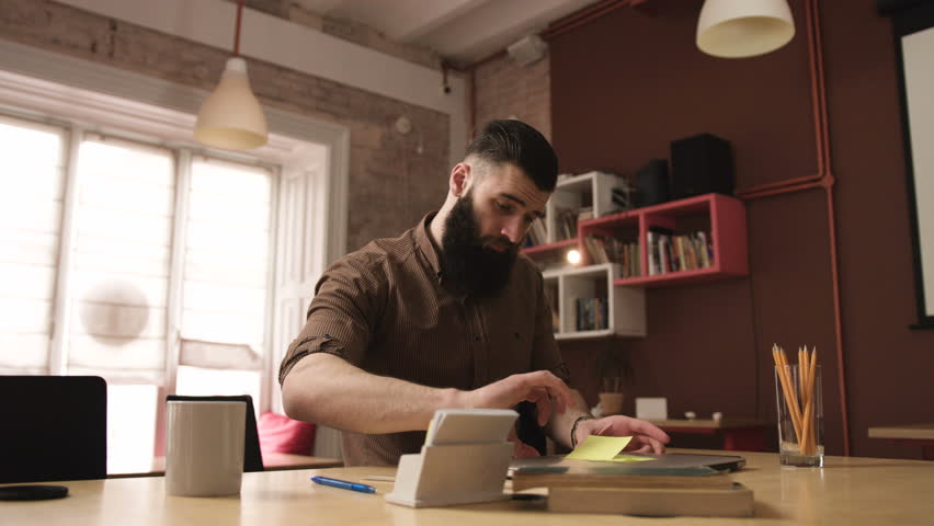 Attractive young bearded man sits down and begins work on a laptop | Shutterstock HD Video #25903055
