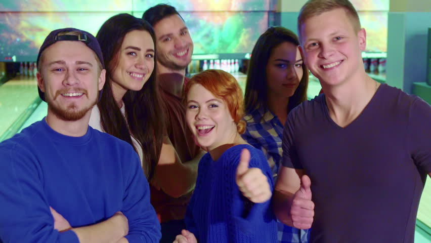 Friends having fun at the bowling. Young people dancing against background of lanes. Close up of attractive teenagers showing their thumbs up