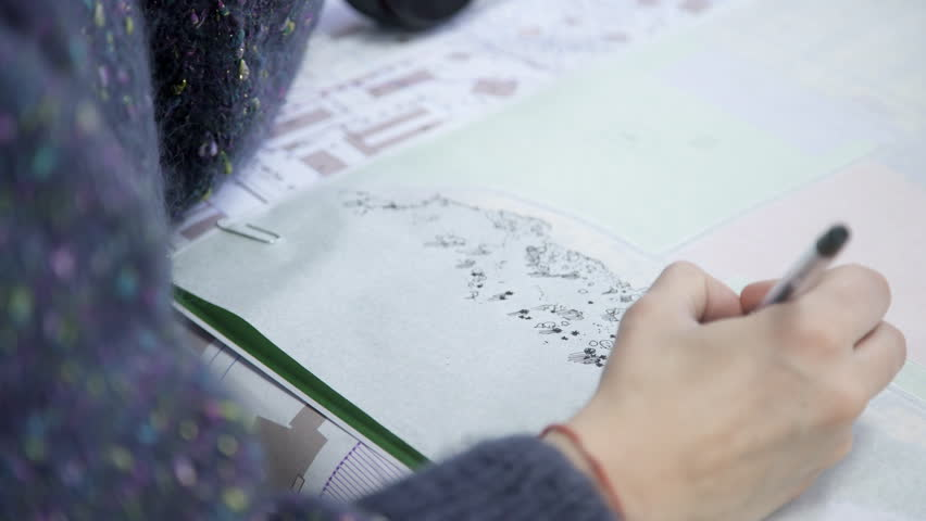 Human in blue sweater makes monochrome pen drawing on paper. Woman with a red thread on her wrist draws the image of small parts on a white sheet. Under the picture is a big drawing.