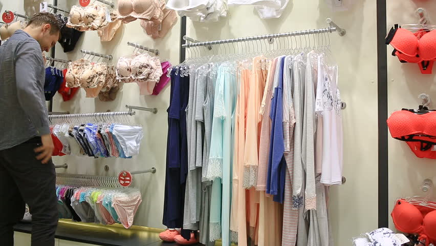 Man chooses panties for a girl in a women's underwear store