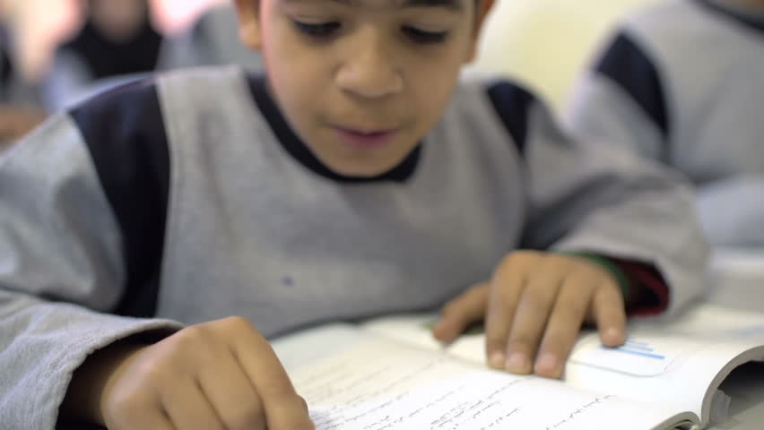 BEIRUT, LEBANON - 2016: A student in 6th grade reads from book inside class. Education in Lebanon is compulsory from age 6 to age 14