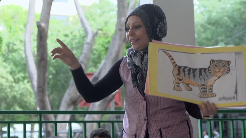 BEIRUT, LEBANON - 2016: Muslim veiled kindregarten teacher interacts with children.