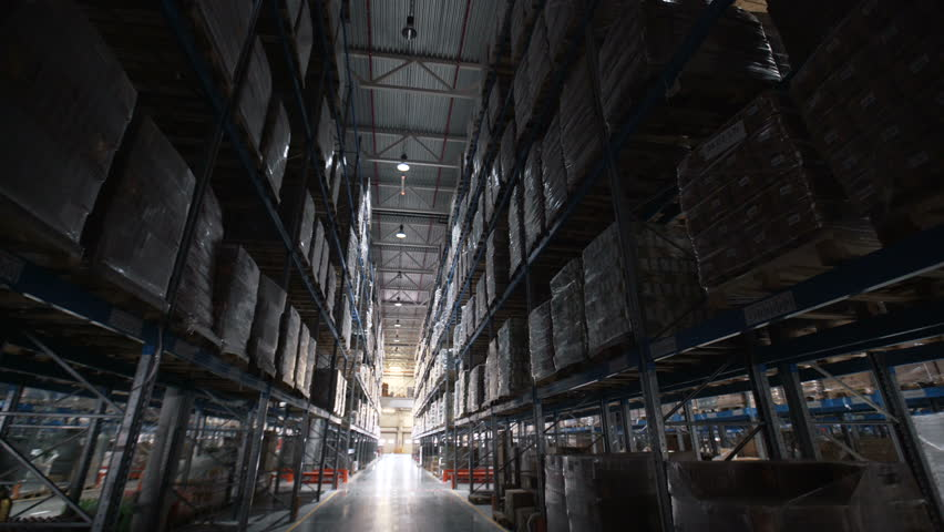 Warehouses large logistics commerce structure with boxes on the shelf. Male person using machine work and vehicle in depot, delivering merchandise for transnational export industry production indoors | Shutterstock HD Video #25957961