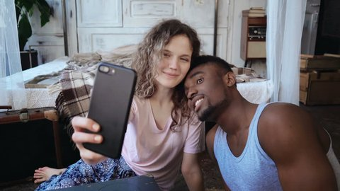 Happy multiethnic couple taking selfie photos on smartphone. Woman and man in pajamas make funny looking face, have fun.