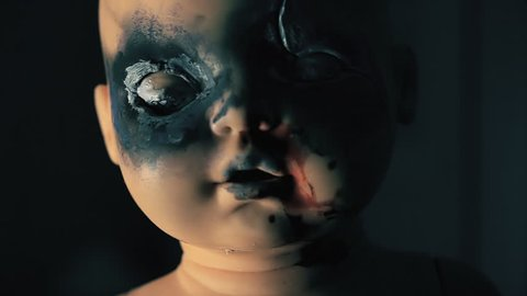 A wicked doll, looking at the viewer, moving its burnt eyes and mouth, wanting to kill.  Halloween horror themed clip.