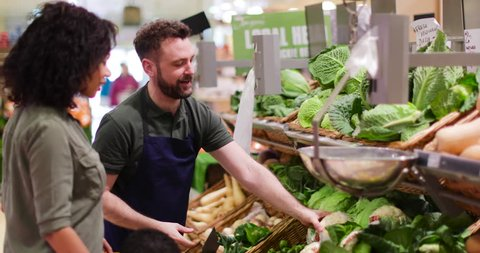 Shop assistant in grocery store helping shoppers