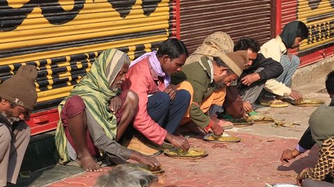 VARANASI, INDIA - JANUARY 25, 2017 : Unidentified poor indian people eating free food at the street near river ganges in Varanasi, India