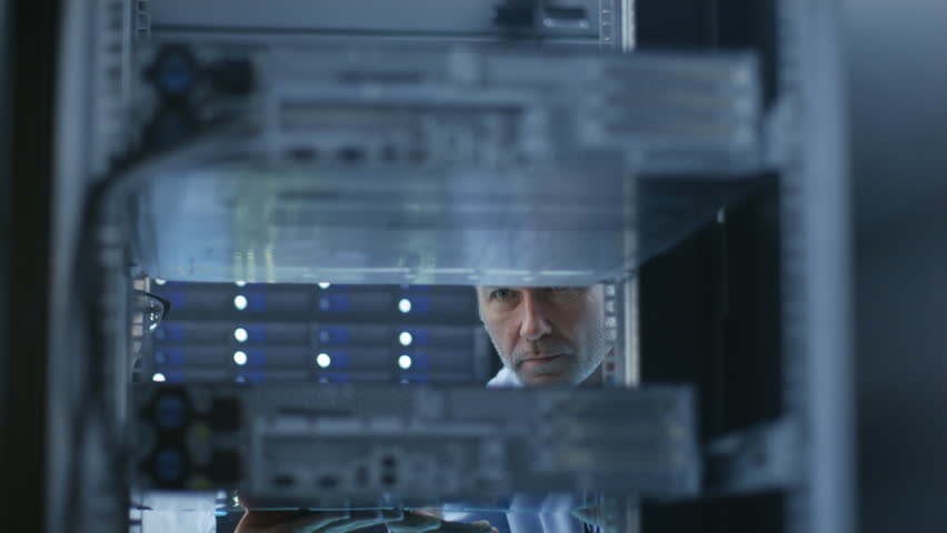 Two Server Technicians Install Hardware in Server Rack. They Work in Big Modern Data Center. Shot on RED EPIC-W 8K Helium Cinema Camera.