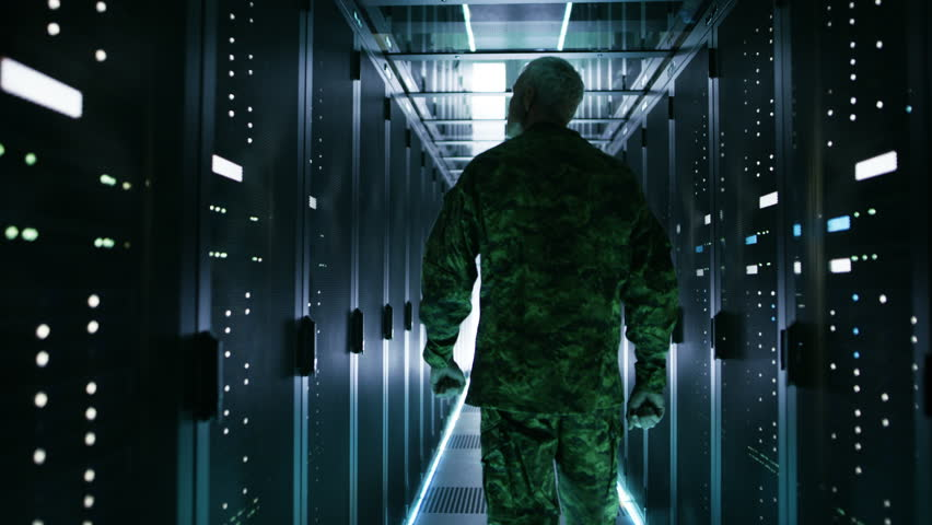 Soldier Walks into Data Center Through Sliding Doors and Walks along Rows of Working Rack Servers. Shot on RED EPIC-W 8K Helium Cinema Camera. | Shutterstock HD Video #26008688