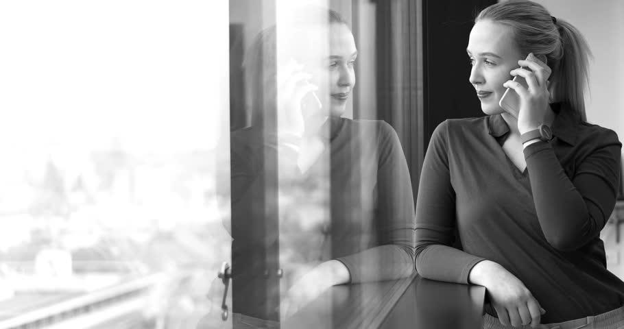 Elegant Woman Using Mobile Phone by window in office building | Shutterstock HD Video #26012321