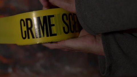 """CRIME SCENE TAPE CLOSE UP.  """"CRIME SCENE DO NOT CROSS.""""  SLOW MOTION SHOT OF MALE HANDS UNROLLING TAPE WITH NONDESCRIPT, RED & BLACK BACKGROUND.  SHOT AT 180 FRAMES PER SECOND."""