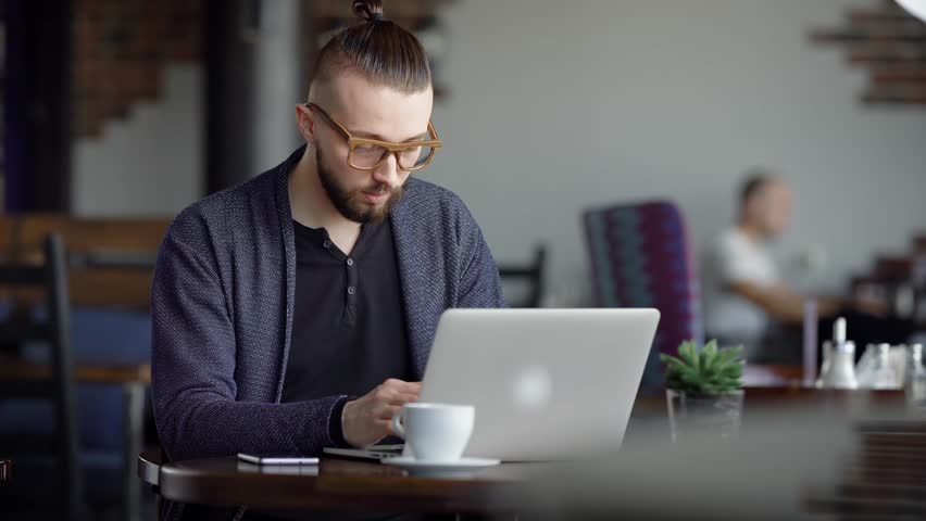 A young attractive hipster in a cafe, with a modern interior. The man works on his stylish laptop. A designer or a writer makes a project in a cafe.