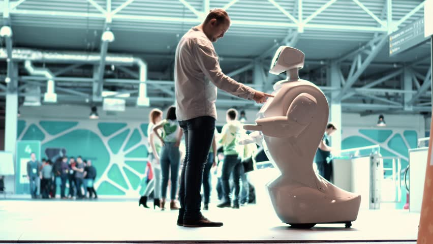 MOSCOW RUSSIA - 04.04.2017: Modern Robotic Technologies. A man communicates with a robot, presses a plastic mechanical arm to the robot, handshake.