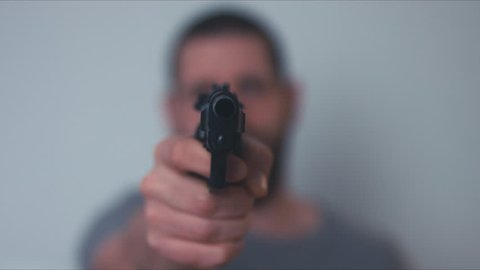 Thug pointing a gun into a camera. 4K UHD RAW edited footage