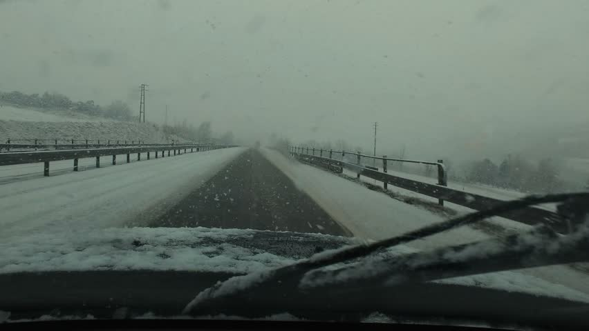 4-wheel car with studded winter tyre runs snow-covered Highway - Point of view, from inside moving vehicle.