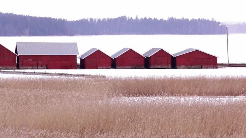Wooden boathouses in light snowfall behind dense bed of reeds in spring 2017 in Kerimaki, Finland.