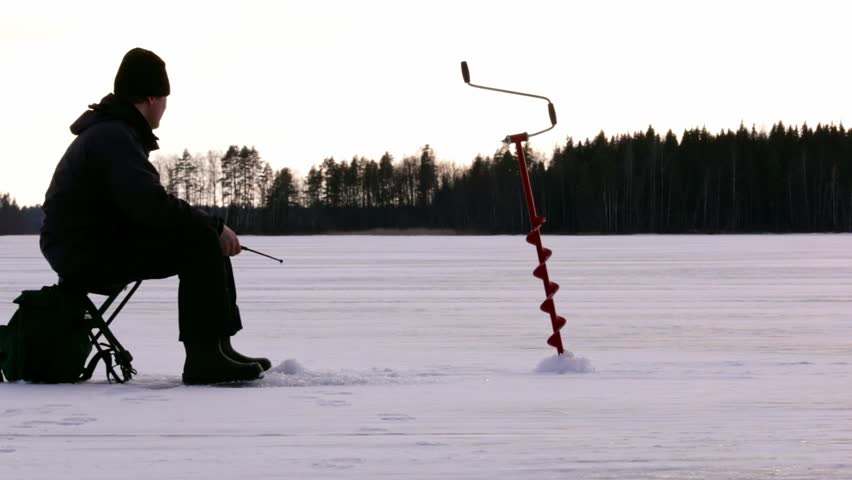 Fisherman ice fishing at a Nordic lake in Finland. Ice auger standing on the ice.