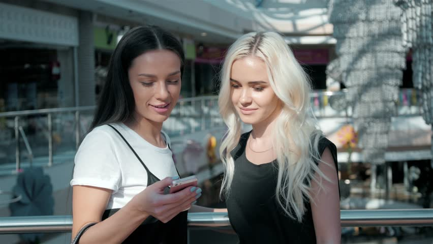 Two beautiful young female shopaholics surfing the internet in search of discounts in shopping mall, young student girls travelling, in airport terminal | Shutterstock HD Video #26086898