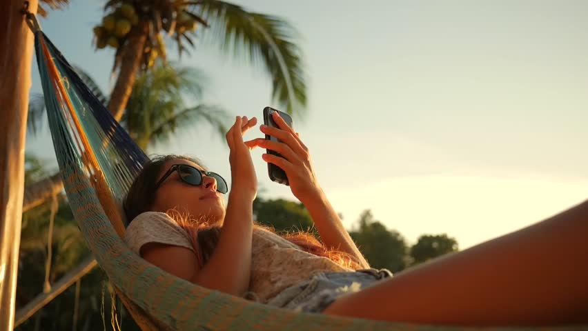 Relaxed Mixed Race Young Woman Looking at Mobile Phone in Hammock at the Beach near the Sea at Sunset. Koh Phangan, Thailand. HD Slowmotion. #26088971