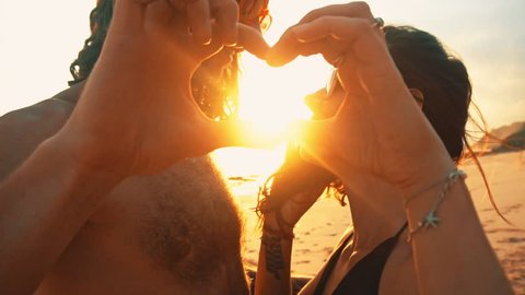 Happy young couple making heart shape with hands at the sunset on at sunset on a lonely beach