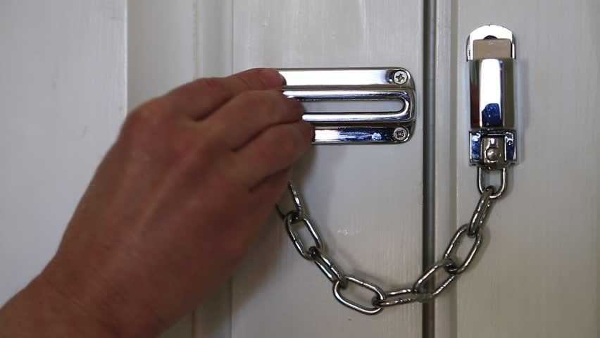 Woman closes door with the safety chain. Hand and door safety chain