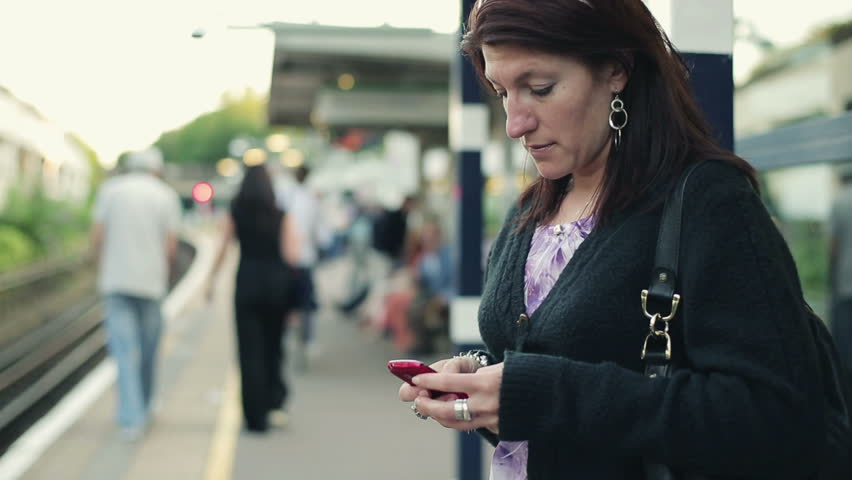 Young woman using smartphone on train station