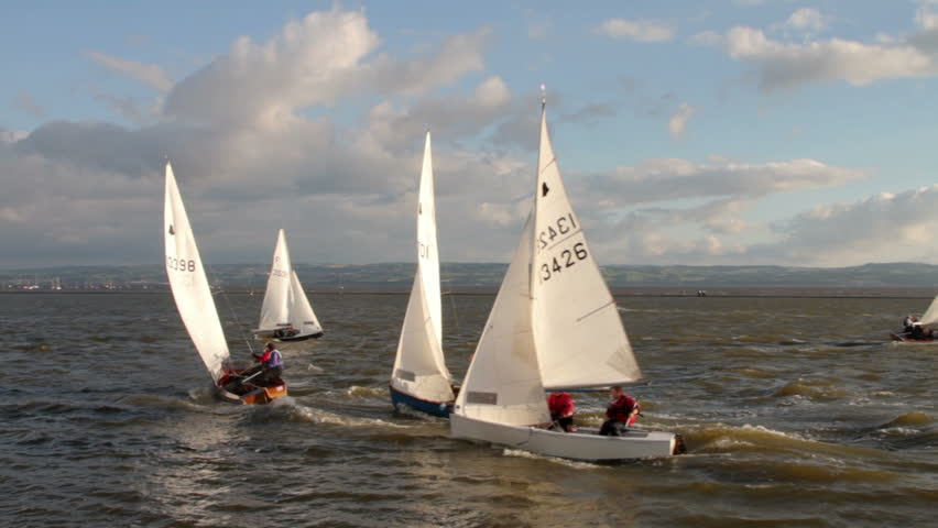 WIRRAL, CHESHIRE/ENGLAND - JUNE 12: Sailing dinghies on West Kirby Marine Lake race past a buoy on June 28, 2012 in Wirral. The Marine Lake is a man made coastal lake fed by the sea at high tide.