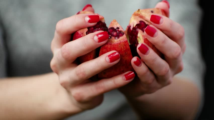 Girl shares a ripe pomegranate. Juice of this fruit is useful to health