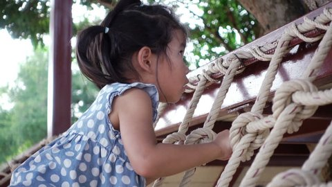Adorable asian little girl be eager to know and slowly stand on climbing frame