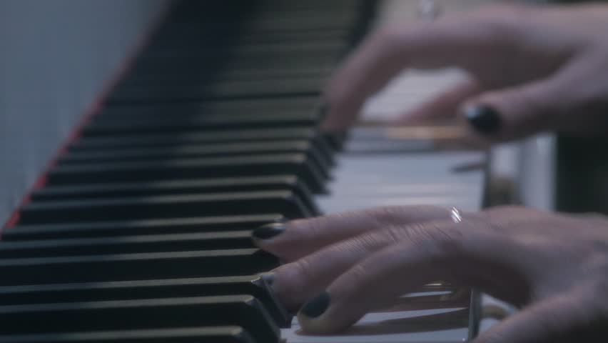 Female arms with rings, black nail polish and red string playing piano in lounge zone, close up dolly shot #26150531