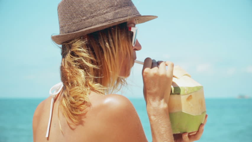Woman drinking fresh coconut water with straw on beach fun vacation. Closeup of woman holding young green tropical fruit sipping for healthy snack during summer holidays in slow motion