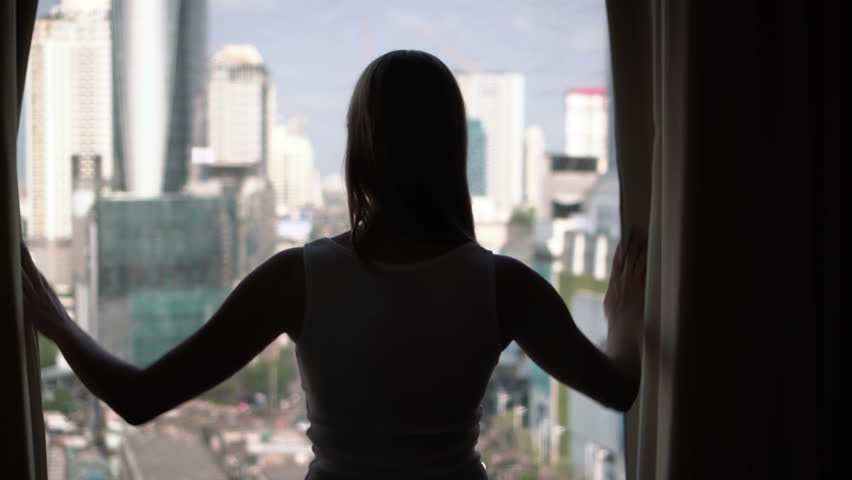 Silhouette of woman unveiling curtains and looking out of window. City skyscrapers landscape outside | Shutterstock HD Video #26153801