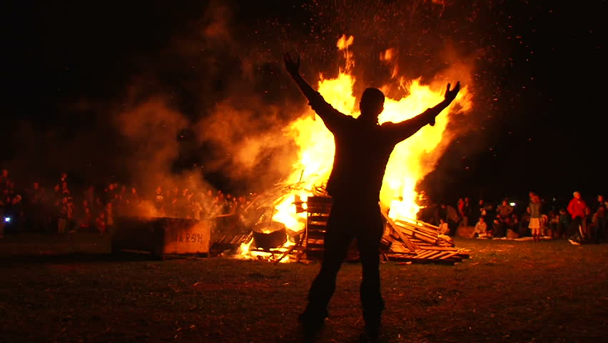 Man in front of large bonfire has both arms up high taking in the heat, filmed