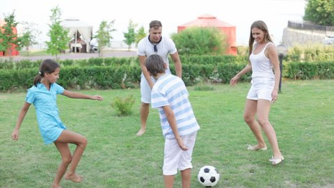 Parents and kids kicking the soccer ball on the countryside lawn