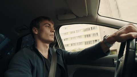 Young caucasian man talks to passenger and change radio stations while driving car through city street using one hand, summer day