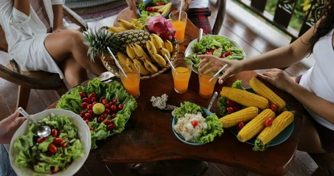 People Clink Juice Glasses, Table With Dishes Of Tropical Fruits And Salad Top Angle View Friends Eating Healthy Vegetarian Food Slow Motion 60