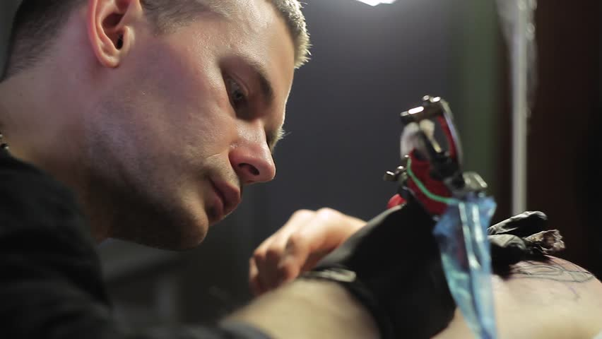 Man tattoo artist makes a tattoo on shoulder in black ink, Close-up shooting | Shutterstock HD Video #26199521