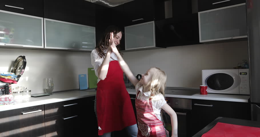 4K An attractive mother and her daughter in the aprons are having fun indoors. A young woman hugs a little girl at the kitchen.