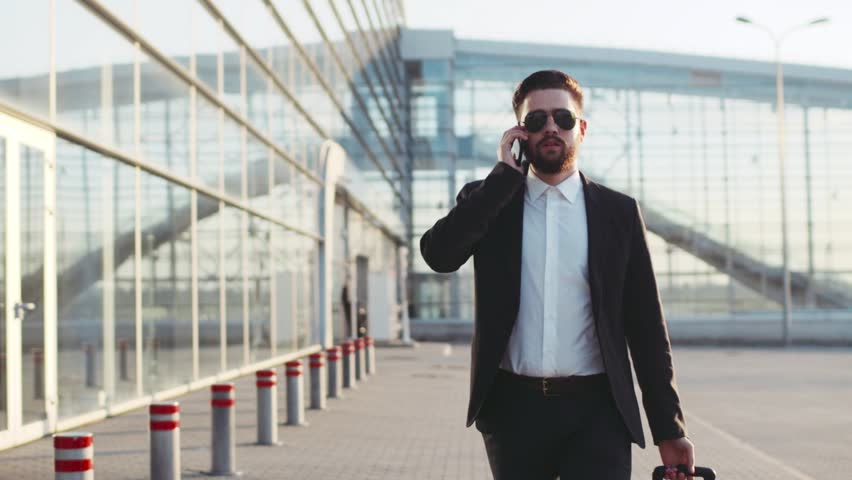 Young stylish man in sunglasses talking on his phone, and pulling suitcase while exiting the airport. Successful life. Business style, traveler, modern lifestyle. Active lifestyle.