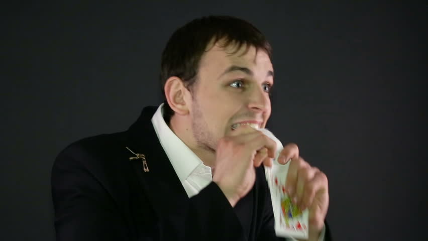 magician shows trick with card on black background.