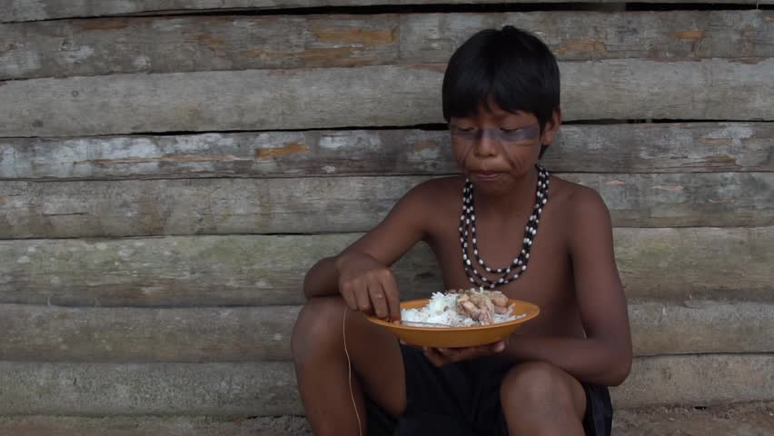 Children eating a traditional food in a indigenous Tupi Guarani Tribe in Brazil