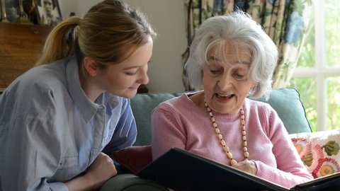 Senior woman sitting with adult granddaughter at home looking through photo album together