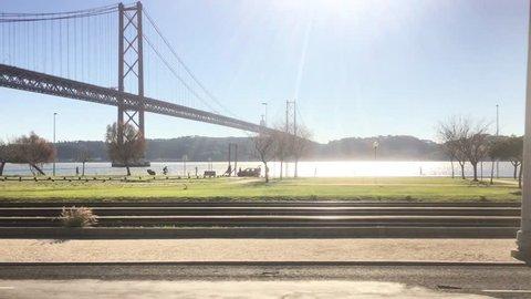 POV Train Ride In Lisbon Along Famous Bridge In Tagus River. POV Train ride through city of Lisbon on a beautiful sunny day